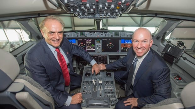Alain Bellemare, right, president and CEO of Bombardier Inc., and Calin Rovinescu, president and CEO of Air Canada, sit in the cockpit of a Bombardier CSeries. Bombardier, which has a deal to sell Air Canada 45 CSeries jets, announced Wednesday it will eliminate 7,000 positions over two years.