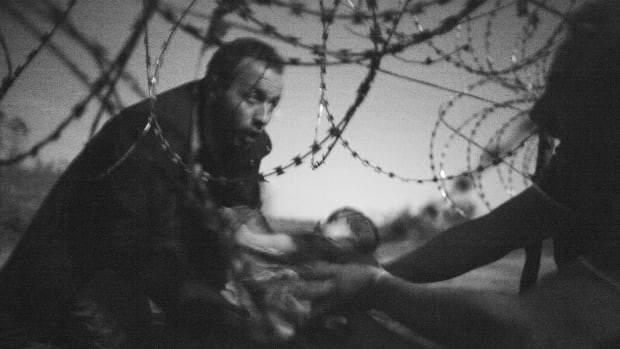 Australian freelance photographer Warren Richardson's image of a refugee handing a baby through a fence at the Serbia-Hungary border won top honours in the prestigious World Press Photo Contest. Winners for 2016 were announced on Feb. 18.