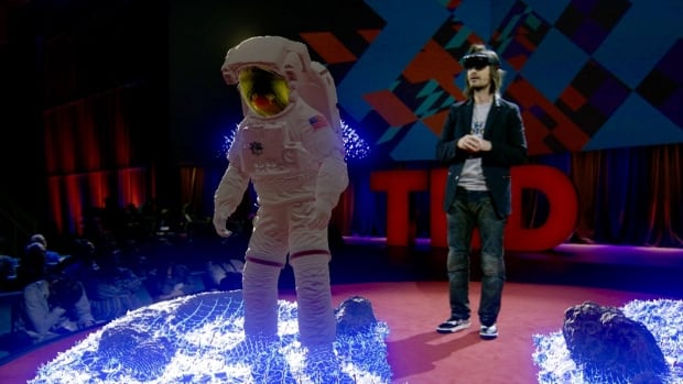 Microsoft's Alex Kipman on the TED stage demonstrating Hololens, the company's augmented reality glasses. The holographic space man is visible via Hololens only to Kipman, but a camera captured that view and projected it in the auditorium.