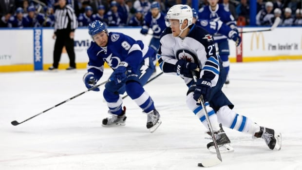 Winnipeg Jets' Nikolaj Ehlers, of Denmark, avoids the check of Tampa Bay Lightning's Tyler Johnson during the first period of an NHL hockey game Thursday, Feb. 18, 2016, in Tampa, Fla.