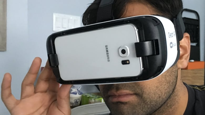 c39242be7585 CBC s Anand Ram tries out the Samsung Gear VR heaset. It has straps to keep  the device mounted to your face and touch controls and buttons add a layer  of ...