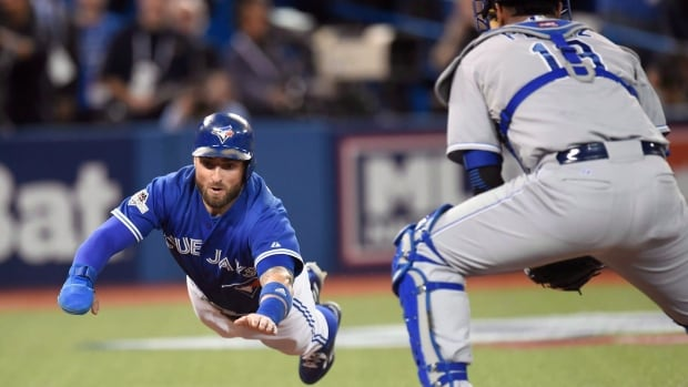 Toronto Blue Jays' Kevin Pillar, left, dives for home plate as he scores in front of Kansas City Royals catcher Salvador Perez during second inning game three American League Championship Series baseball action, in Toronto on October 19, 2015.