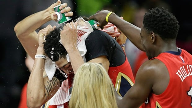 New Orleans Pelicans guard Jrue Holiday pours water on forward Anthony Davis after their win over the Detroit Pistons on Sunday in Auburn Hills, Mich.
