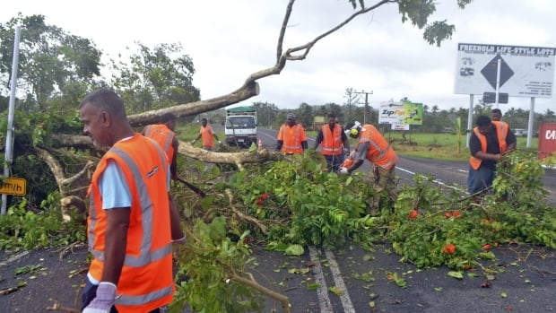 Road workers remove a fallen tree blocking a road near Lami, Fiji, on Sunday, after Cyclone Winston ripped through the country. Officials in Fiji are assessing damage in the wake of the ferocious cyclone that tore through the Pacific island chain.