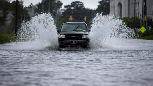 A motorist drives through the brackish sea water that seeps low lying areas in Charleston, S.C. Nuisance flooding, which is from ordinary high tides exacerbated by sea level rise and accompanying land subsidence, is increasing in part due to sea level rise from man-made climate change.