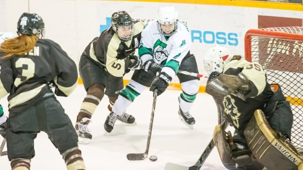 Lindsay Blight of the University of Manitoba Bisons battles for the puck as goalie Amanda Schubert prepares to make one of 66 saves during a historic five-overtime game against the University of Saskatchewan Huskies in Saskatoon on Sunday.