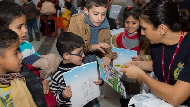 Acting Sgt. Lina Dabit, of the RCMP interacting with children at the processing centre in Amman, Jordan on January 10, 2016.