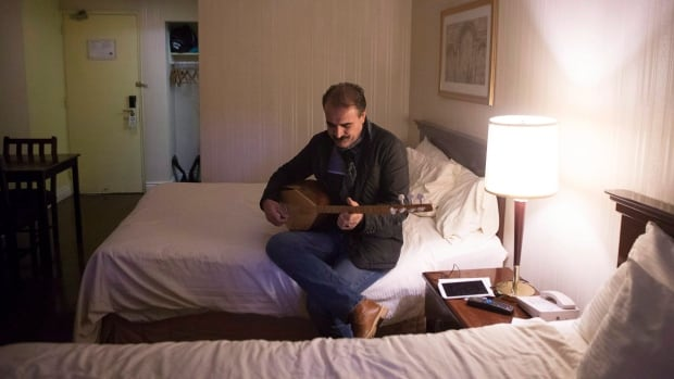 Syrian Kurdish refugee Dilaver Omar plays the tamboor as he sits in his family's room at a Toronto hotel being used to house government-sponsored refugees as they wait for permanent accommodation.