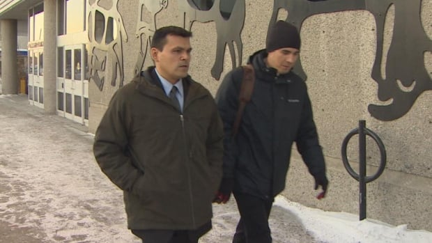 Colin Allooloo, left, leaves the Yellowknife courthouse Feb. 23 during his trial on charges of sexual assault and sexual interference.