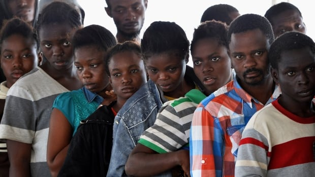 Migrants and refugees, mainly from Nigeria, Ghana, Senegal and Sierra Leone, after being rescued at sea, wait to receive food on a German navy ship in September 2015. Advocates Daniel Tseghay and Josiane Anthony say African refugees are being forgotten by Canada.