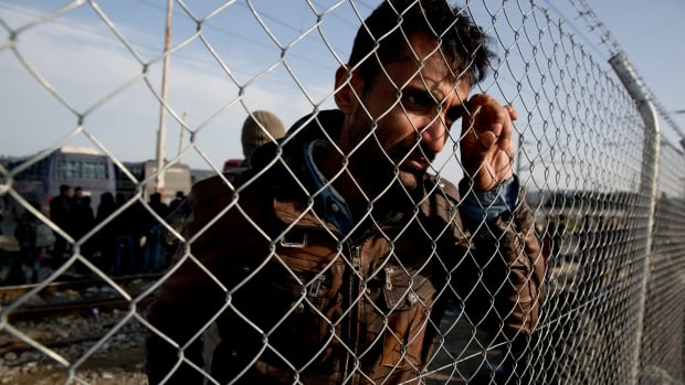 An Afghan migrant waits behind a fence on Tuesday in the northern Greek border station of Idomeni to board a bus bound for Athens.
