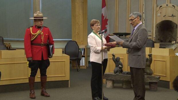 Emiliano Qirnuq swears an oath with Nunavut Commissioner Nellie Kusugak in Nunavut's legislature Wednesday Feb. 24.