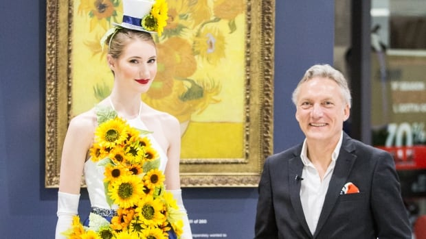 Willem van Gogh (right) stands in front of a 3D reproduction of Vincent van Gogh's paintings of sunflowers. With him is a model in a dress that pays tribute to van Gogh's sunflowers