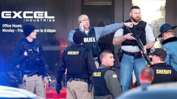 Police guard the front door of Excel Industries in Hesston, Kan., Thursday, where a gunman killed an undetermined number of people and injured many more.