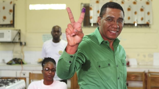 Andrew Holness, leader of the opposition Jamaican Labour Party, shows his ink-stained finger after casting his vote at a polling station Thursday in Kingston.