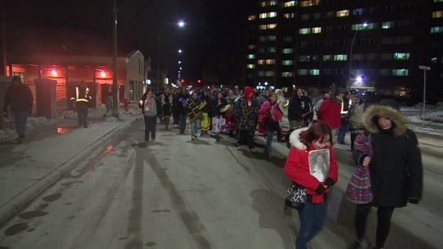 A crowd walks in the North End of Winnipeg on Thursday evening to remember Marilyn Rose Munroe, whose body was found inside a house on Pritchard Avenue on Monday.