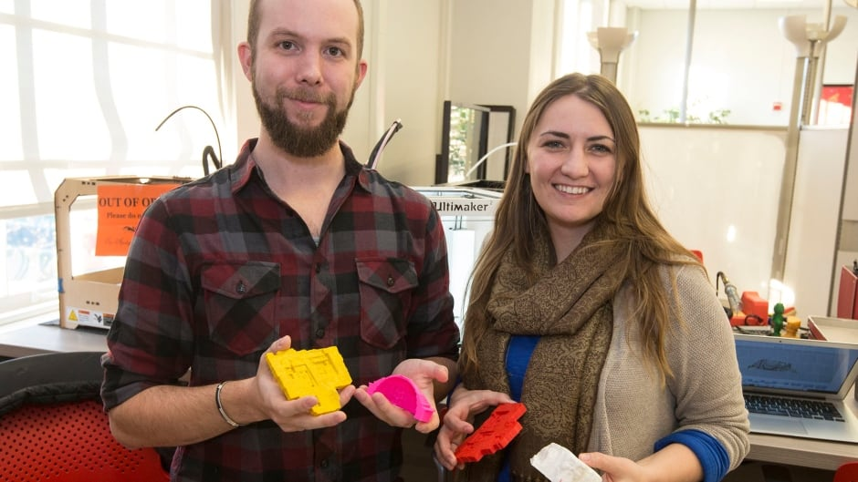Graduate students Jennifer Grayburn and Benjamin Gorham hold examples of artifacts and archaeological dig sites they've recreated using an Ultimaker 3D printer