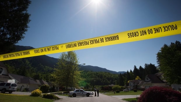 RCMP officers talk during the investigation of multiple homicides in Rosedale, east of Chilliwack, B.C., on Friday May 8, 2015. THE CANADIAN PRESS/Darryl Dyck