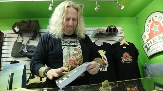 Alan Amsterdam, a co-owner of the Capitol Hemp shop in Washington's Adams Morgan neighbourhood, unseals a packet of Green Love Potion, which he cultivated in his own grow room at home.
