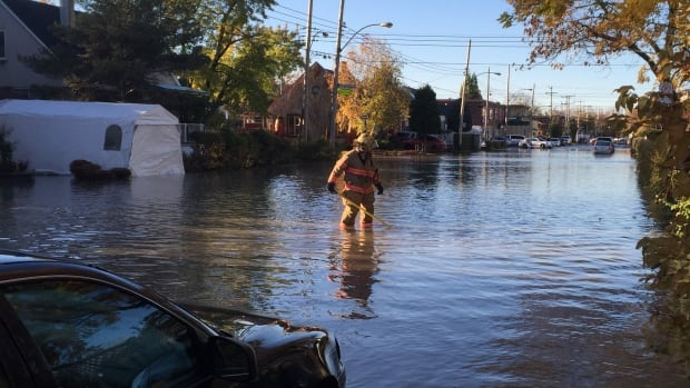 A Montreal firefighter wades through a flooded street after a major water main break in October.