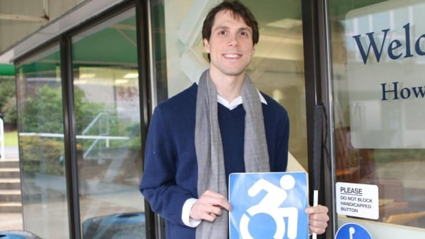 Richard Harlow holds the updated accessible icon.