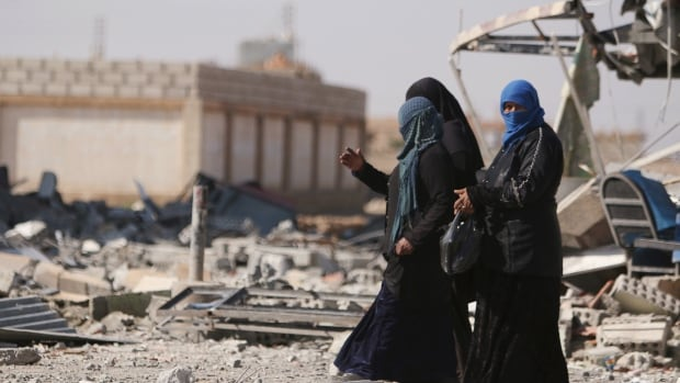 Women walk on rubble in al-Shadadi town, in Hasaka province, Syria on Friday.