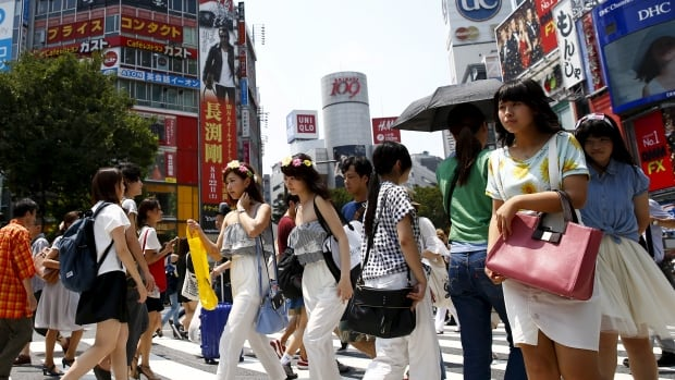 People cross a junction in front of advertising billboards in the Shibuya shopping district in Tokyo last July. Japan's population has fallen for the first time since their five-year census began in 1920.