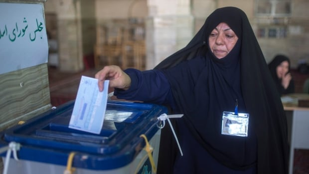 An Iranian woman votes in the parliamentary and Experts Assembly elections at a polling station in Qom, Iran on Friday.