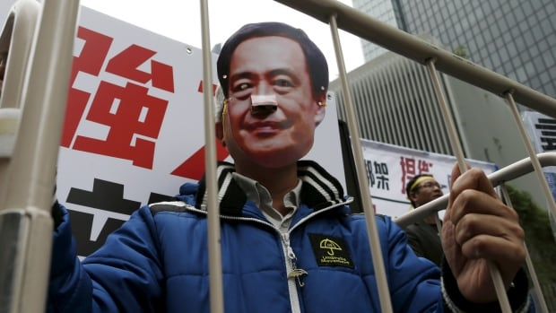A demonstrator wears a mask depicting Causeway Bay Books shareholder Lee Bo during a protest over the disappearance of booksellers, in Hong Kong, China January 10, 2016.