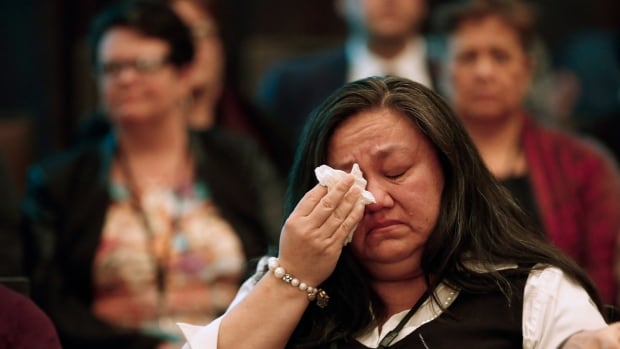 A woman wipes away a tear around a sharing circle at the roundtable on missing and murdered indigenous women and girls in Winnipeg on Feb. 25.