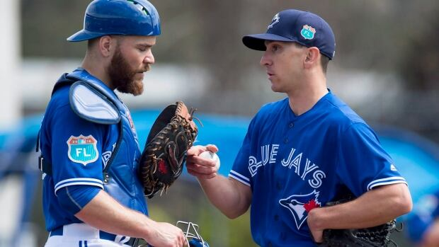 Toronto Blue Jays pitcher Pat Venditte and catcher Russell Martin chat on the mound during an intersquad game at spring training in Dunedin, Fla. on Monday, Feb. 29, 2016.