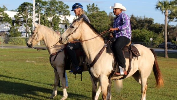 New York Mets' Yoenis Cespedes and Noah Syndergaard ride horses at the team's spring training baseball facility.