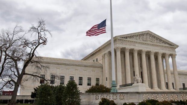 In this Feb. 25, 2016, file photo, in honor of Justice Antonin Scalia, a flag in the Supreme Court building's front plaza flies at half-staff in Washington.
