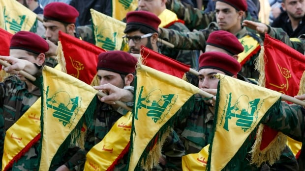 Members of Hezbollah hold their flags on March 1, 2016, in the southern Lebanese town of Kfour, during the funeral of a fighter killed in Syria. A group of Arab states on Wednesday labelled Hezbollah as a terrorist organization.