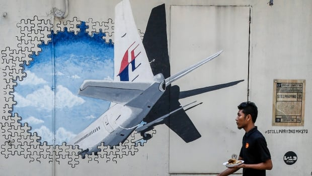 A waiter walks past a mural of flight MH370 in Shah Alam outside Kuala Lumpur, Malaysia in this February 2016 file photo.