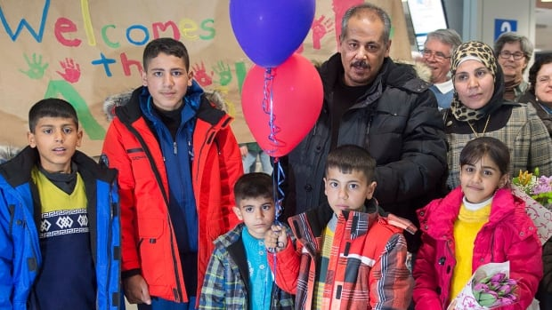 The Ayash family from Syria pose for a photograph after arriving in Halifax on Monday. The family is being sponsored by a community group in Lunenburg, N.S., and will soon move into a home in the historic town.