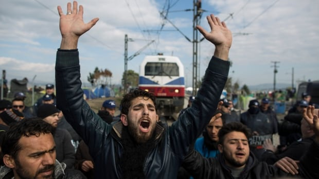 A refugee man pleads with a group of other men to calm down as a train attempts to pass at the Greek-Macedonia border on Thursday in Idomeni, Greece. A transit camp at the border is becoming increasingly overcrowded as thousands of refugees continue to arrive from Athens and the Greek islands.