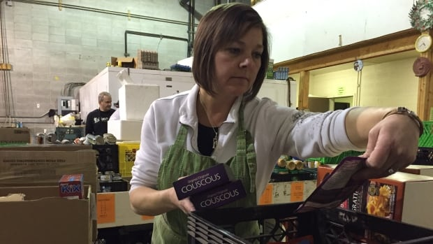 A volunteer at the Red Deer food bank sorts donations. The agency has seen some staggering increases in demand in February 2016 compared with the same month last year.