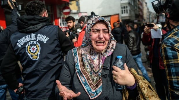 A woman cries as anti-riot police officers disperse supporters in front of the headquarters of the Turkish daily newspaper Zaman in Istanbul on Sunday.