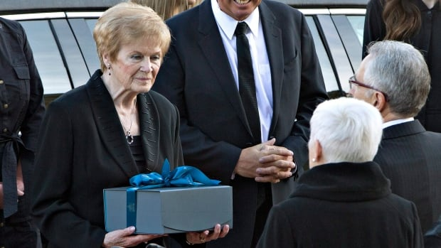 Margaret Getty, wife of former Alberta premier Don Getty, receives a box with the Alberta provincial flag in it during the procession for Getty's state funeral on Saturday.