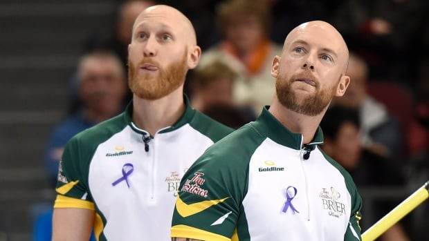 Northern Ontario teammates Brad Jacobs, left, and Ryan Fry check out the scoreboard during their game against Saskatchewan at the Brier. Northern Ontario won 6-5 in an extra end.