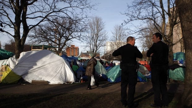Victoria Police watch over residents at the homeless camp, also known as InTent City, during a block party at the camp in Victoria, B.C. on Thursday, Feb. 25.