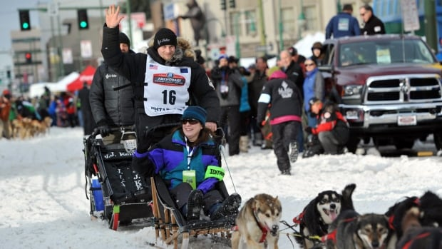 Defending Iditarod Trail Sled Dog Race champion Dallas Seavey waves to the crowd at the start of the 1,600-kilometre race in Anchorage, Alaska. Seavey won his third straight race early Tuesday morning.