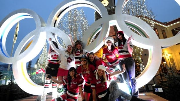 Fans pose in front od the Olympic Rings in Whistler Ski Resort village, in preparation for the Vancouver Winter Olympics on February 11, 2010.