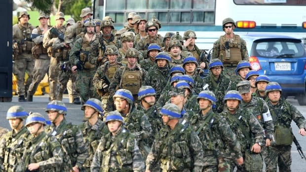 South Korean marines, wearing blue headbands on their helmets, and U.S. marines move together during the annual joint military exercise Key Resolve and Foal Eagle by South Korea and the United States in Pohang, South Korea, on Monday.