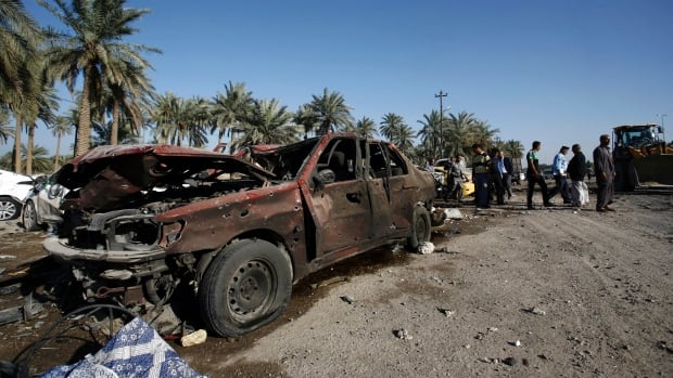 Iraqi emergency responders on Sunday clear debris from the site of a truck bomb, that exploded at a crowded checkpoint, in the Iraqi city of Hilla, south of Baghdad.