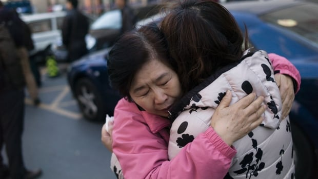 Two relatives of Chinese passengers who were aboard missing Malaysia Airlines flight MH370 cry as they leave the Beijing Rail Transportation Court in Beijing on Monday. Relatives of a dozen Chinese passengers aboard the flight began filing suits against the airline in a Beijing court on Monday, a day ahead of the second anniversary of its disappearance and a legal deadline.