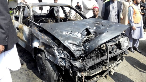 A damaged car sits at the site of a suicide attack at a sessions court compound in Shabqadar, northwestern Pakistan on Monday.