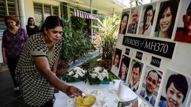 A school teacher lights a candle as she pray for passengers of missing Malaysia Airlines flight MH370 in Petaling Jaya, Malaysia on Tuesday.