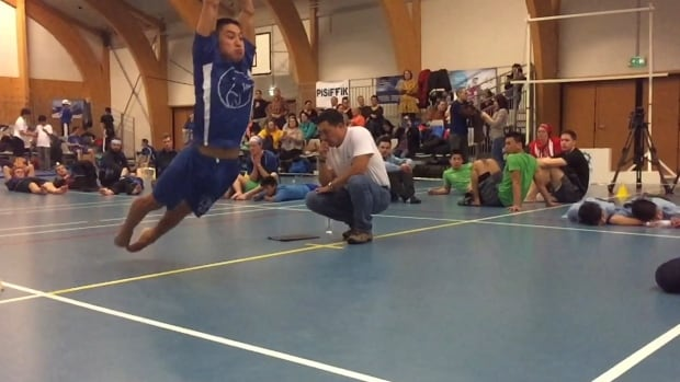 Inuvik, NWT athlete James Day Jr. explodes off the line during the kneel jump competition at the Arctic Winter Games in Nuuk, Greenland.